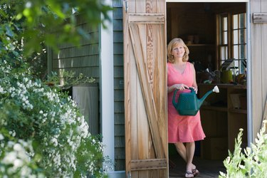 Woman with watering can posing in doorway