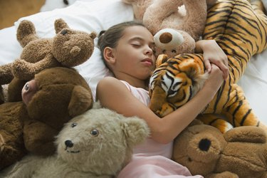Hispanic girl sleeping in bed surrounded by stuffed animals