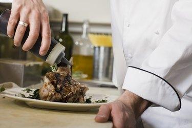 Chef drizzling garnish over pork chops