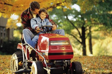Father and son on riding mower
