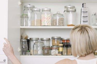 Woman opening kitchen cupboard