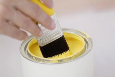 Human hand holding a paint brush over a paint can