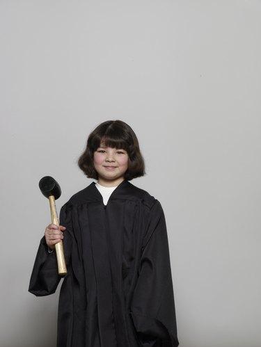 Girl (5-7) wearing judicial robe, holding gavel, portrait