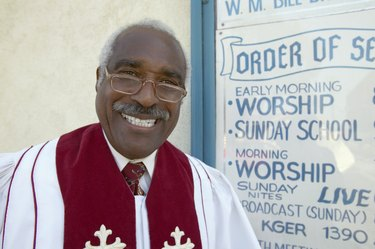 Portrait of a Smiling Priest Standing by a Notice Board