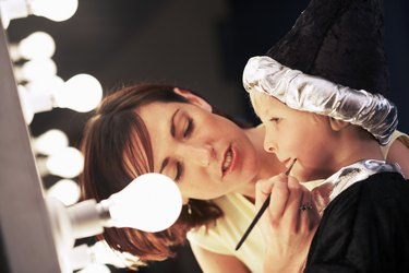 Teacher applying make-up to boy (3-5) in wizard costume backstage