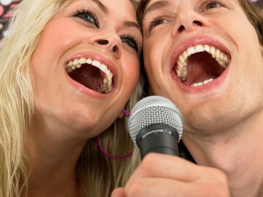 Young woman and man singing into microphone, close-up, low angle view