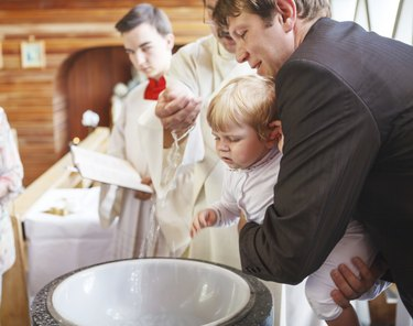 Little baby boy being baptized in catholic church holding