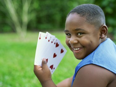 Side profile of a boy holding cards