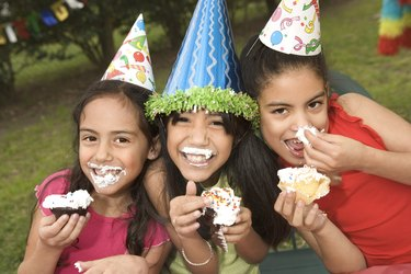 Girls with messy birthday cake at party outdoors