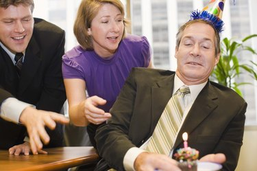 Co-workers and businessman with party hat and cupcake