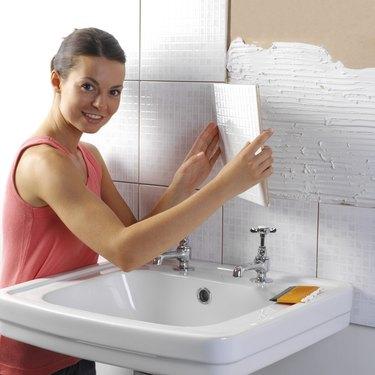 Woman tiling bathroom wall