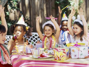 Group of children sitting at a table at a birthday party with their arms raised