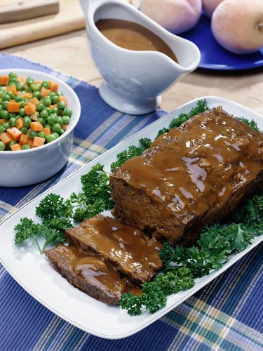 Meatloaf, gravy, mixed vegetables, and bread sitting on a table