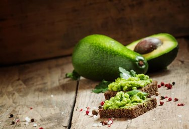 Sandwiches with black rye bread and avocado mousse with spices, selective focus