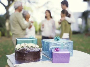 Gifts and birthday cake on table, close up, family in background
