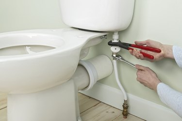Using slip-joint pliers to brace inlet pipe
