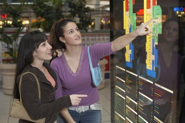 Two teenage girls looking at a map in a shopping mall