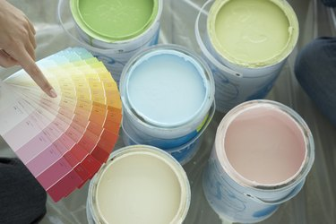 Hand pointing to paint colors above paint cans
