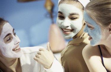 Three teenage girls wearing facial masks