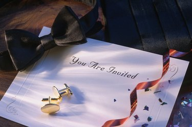Bowtie and cuff links on top of invitation
