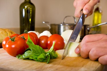 Chef's Hands Slicing an Onion