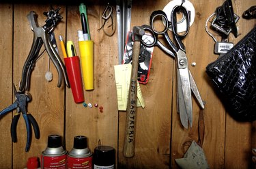 Tailor's tools hanging on wooden panel, close-up