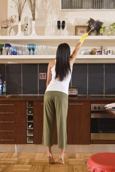 Woman dusting with feather duster