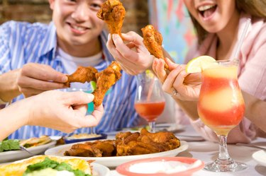 Party of people eating hot wings