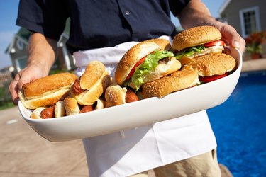 Man holding tray piled with hot dogs and hamburgers
