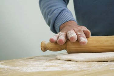 Man preparing dough with rolling pin, close-up