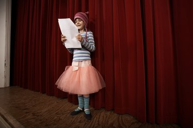 Girl (5-7) practicing lines on stage