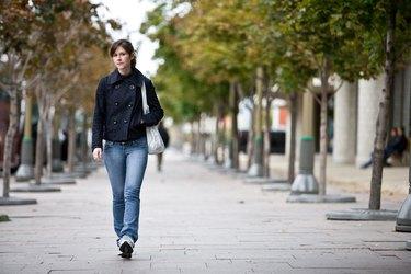 Woman walking on sidewalk in park