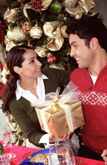 Woman handing man gift at dinner table by christmas tree