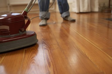Man polishing wooden floor, low section