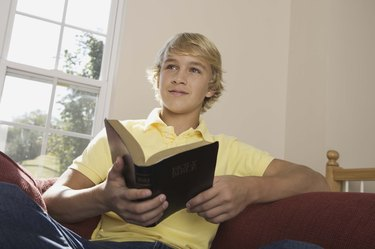 Boy holding Holy Bible indoors