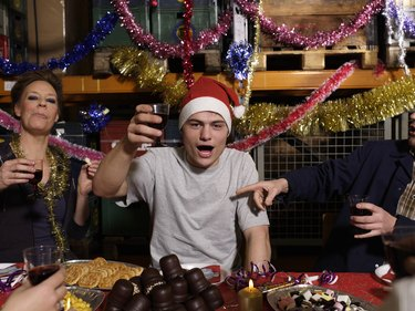 Group of workers toasting with wine glasses at Christmas table in warehouse, portrait