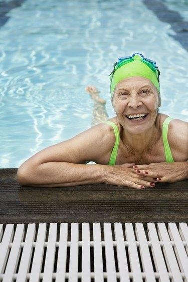 Smiling senior woman swimmer in pool