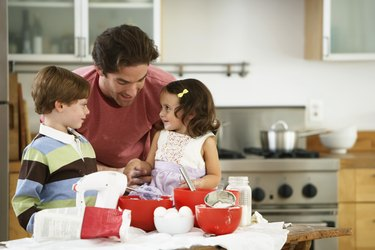 Father, son (5-7) and daughter (2-4) baking in kitchen