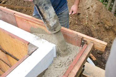 Construction worker pouring concrete in wall mold