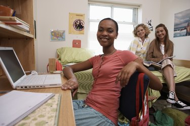 Young women smiling in dorm room, portrait, close-up