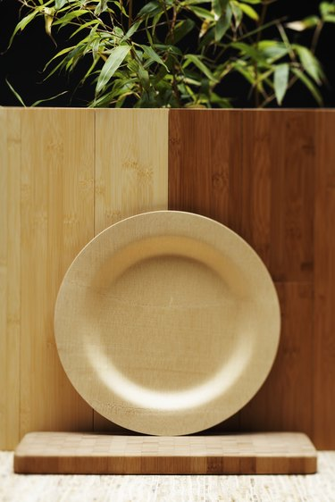 Bamboo plate, cutting board and flooring beside bamboo plant