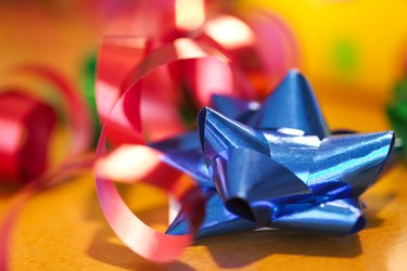 Birthday still life close-up of a blue bow and red ribbon