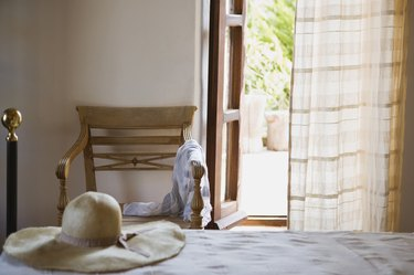 Hat on bed by open window