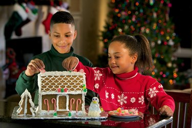 A brother and sister decorate a gingerbread house at Christmastime.