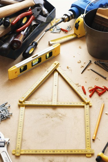 Adjustable rule forming 'house-shape' amongst tools on wooden surface