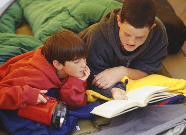 Two brothers (10-14) lying in sleeping bags, reading book in tent