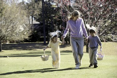 Mother walking on a lawn with her son and daughter