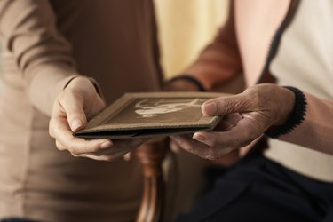 Senior woman and young woman holding old photograph, mid section, close-up of hands