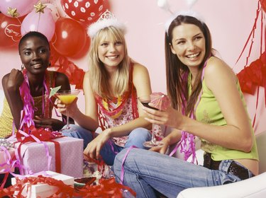 Three young women looking away from camera with drinks at party