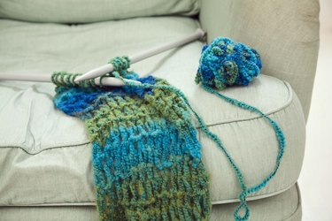 Knitting needles and scarf on chair